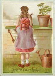 child reaching up to grasp puppy off gardening bench