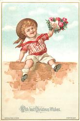 child in red and white sailor suit sits on wall, posie of flowers in left hand