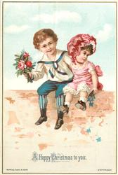boy in blue sailor suit with posie sits with girl in red dress on brick wall