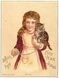 girl in red dress with white pinafore hold cat with blue collar and leash