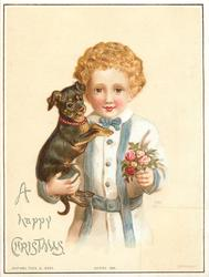 boy in white shirt with blue stripes holds black and brown dog with red collar in one arm and flowers in other hand