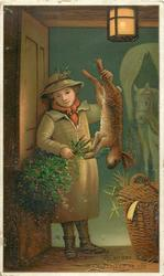 boy in doorway holding up dead rabbit in one hand and holly in the other