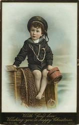 boy in sailor suit holds bucket