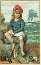 child sits on rocks at shore with shovel and bucket,  sailboat in distance