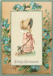 girl in pink dress and wide brimmed hat pulls branch of flowers, blue flowers to floral border