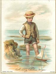 boy stands in water watching toy sailboat