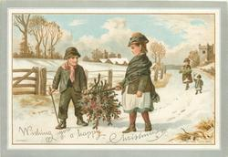 girl and boy carry holly suspended on a branch between them