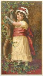 girl in white dress and red sash picks at ivy vine