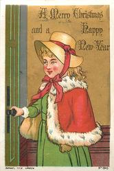 girl in green dress with red cape and brown hat holds doorknob