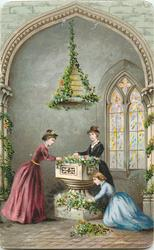 three women decorating large urn with holly and greenery