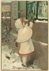 girl in white hat, shawl, and coat placing holly on oustside window ledge