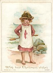 girl in pink and white dress holds shovel behind her back