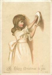 girl in white dress holds up tambourine