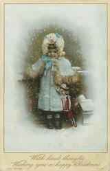 child in winter coat and hat stands with doll