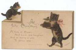 one cat walking on hind legs carrying Christmas pudding, another cat top left corner