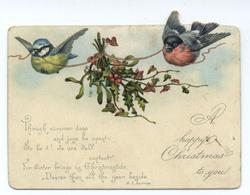 two birds fly with garland around a bouquet of holly and berries