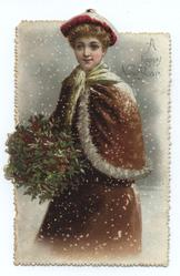 young lady in hat and cape holds bouquet of holly and mistletoe