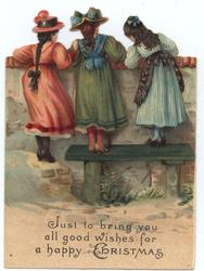 three girls in dresses stand to look over top of fence