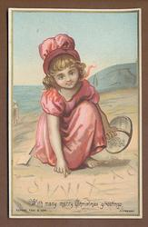 girl on beach, writing in sand, red dress