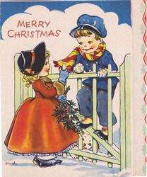 MERRY CHRISTMAS girl and boy speak across gate, girl holds holly