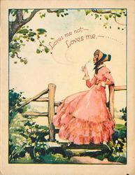 LOVES ME NOT- LOVES ME, - ...... woman in bonnet & pink dress leans against fence, facing & looking left, blowing seeds of dandelion
