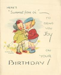 "HERE'S ""SUMMET FROM OI"" TO BRING YOU JOY ON YOUR BIRTHDAY!  two small children face eachother, girl in green coat left, boy in red jacket and blue cap right"