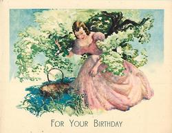 FOR YOUR BIRTHDAY woman in pink dress kneels under tree, her right arm in the branches, basket with handle left