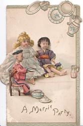 A MERRIE PARTY below 3 Japanese dolls seated facing right, pottery right & above