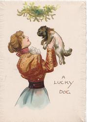 A LUCKY DOG  woman in brown blouse holds ugly puppy up under mistletoe