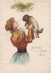 SWEET I LOVE YOU  woman in brown blouse holds ugly puppy up under mistletoe