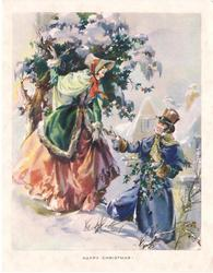 HAPPY CHRISTMAS! couple in old style dress gather holly, houses in background, snow