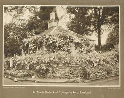 A FLOWER BEDECKED COTTAGE IN RURAL ENGLAND