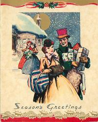SEASON'S GREETINGS couple in old style dress with parcels, gilt moon, snow falls, gilt strip with holly above & gilt holly below