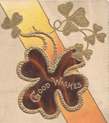 GOOD WISHES on gilt-edged stylised clover in front of printed yellow/orange ribbon, cream background