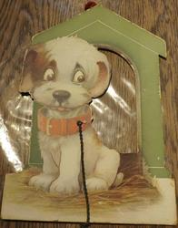 white dog with large red collar sits before a dog house