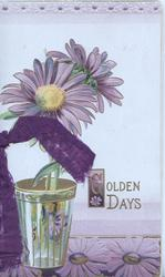 GOLDEN DAYS in gilt, 2 purple daisies with yellow centres standing in glass on purple basal design