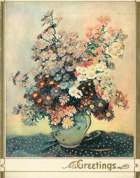 GREETINGS in gilt, many colours of asters in jug with handle, on fabric