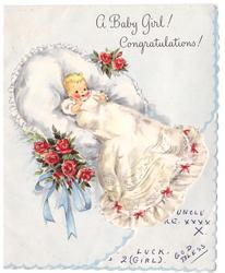 A BABY GIRL! CONGRATULATIONS! baby wears long white dress with red bows, large pillow behind with roses at sides