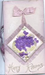 HAPPY RETURNS in gilt, violets on silk cushion applique with fringe. pale pink background