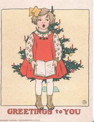 GREETINGS TO YOU in red below girl standing holding book & singing in front of xmas tree