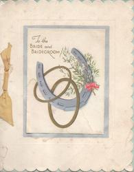 TO THE BRIDE AND BRIDEGROOM! above blue horseshoe, 2 gilt rings & white heather inset with blue border