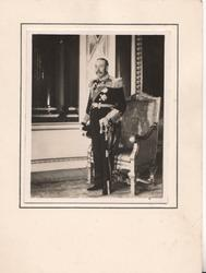 no front title, the King in full uniform stands in front of chair facing left front