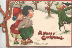 A MERRY CHRISTMAS in red below boy & girl in snowy field scared by crow & impressive scare-crow WHO'S AFRAID!