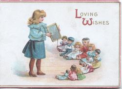 LOVING WISHES in gilt, dolls sit in half circle on floor in front of young teacher holding slate