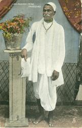 AN INDIAN TYPE, holy man wearing white, hat & full robes,bare feet, right arm on touching pedestal