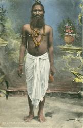 AN INDIAN TYPE holy man wearing white below waist robe, many beads