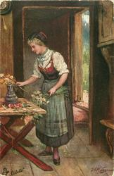 FRISCH GEPFLUCKT  woman stands at table arranging flowers, open door back right
