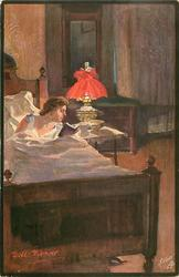 woman lies in bed reading by light from bed-side lamp