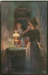 woman looks at image in mirror, lit by oil lamp