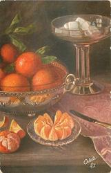 several oranges in brass bowl, peeled slices on glass dish, glass stand with cookies behind right, table-knife right foreground